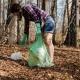 Symbolbild Person sammelt Müll im Wald